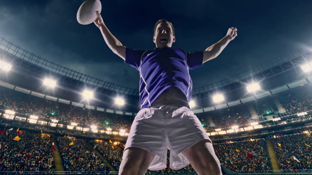 Rugby player jumps with a ball 4K video of a Professional rugby player is cheering on a professional sports stadium. The stadium is made in 3D with animated crowd. rugby stock videos & royalty-free footage