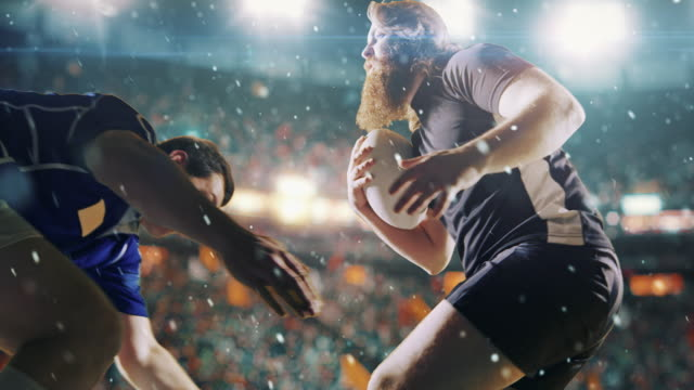 Rugby player jumps with a ball Professional rugby player runs with a ball but is blocked by the opposite team player. The action takes place on a professional sports arena with bleaches full of people. Arena and people on it are made in 3D and animated. rugby stock videos & royalty-free footage