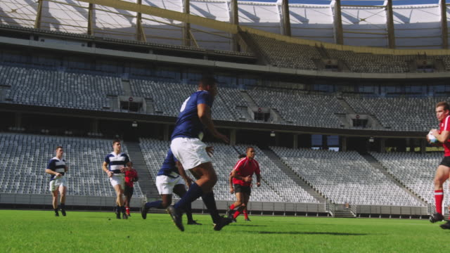 Rugby players playing rugby match in stadium 4k Side view of diverse rugby players playing rugby match in stadium. They are tackling each other other 4k rugby stock videos & royalty-free footage