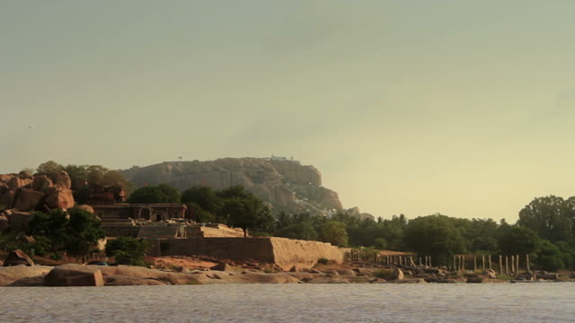 Ruins of a hindu temple seen across a river. video