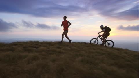vídeos y material grabado en eventos de stock de ts de corredor y ciclismo de montaña en la meseta en atardecer - actividades recreativas