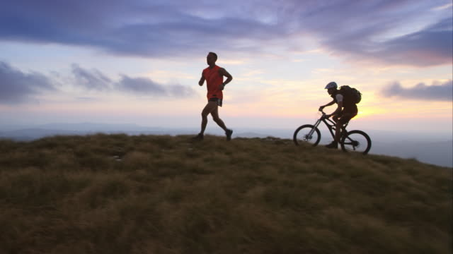 TS runner and mountain biker on the plateau at sunset Medium tracking shot of a mountain biker and runner on a mountain top as the sun is setting. recreational pursuit stock videos & royalty-free footage