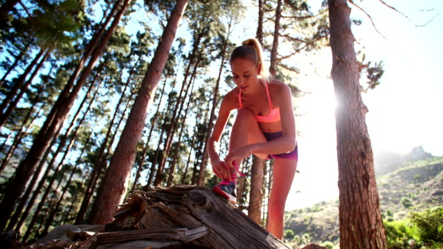 Runner bending over and tying her shoelaces on nature trail video