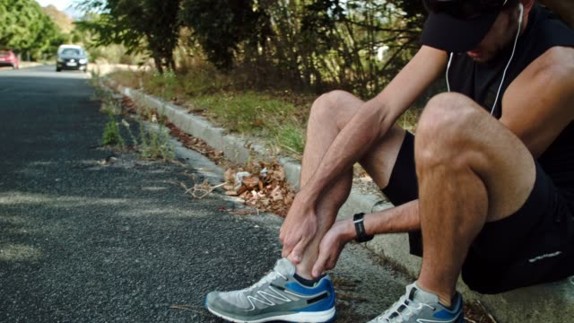 Runner checking ankle injury in road Marathon runner training injury ankle twist physical injury stock videos & royalty-free footage