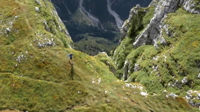 aerial runner running on a mountain top overlooking the valley below and the surrounding mountains - словения стоковые видео и кадры b-roll