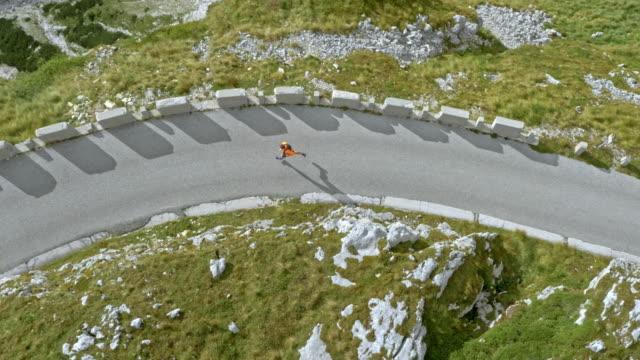 stockvideo's en b-roll-footage met luchtfoto runner uitgevoerd op een weg in een hoge bergketen op een zonnige dag - er even tussenuit