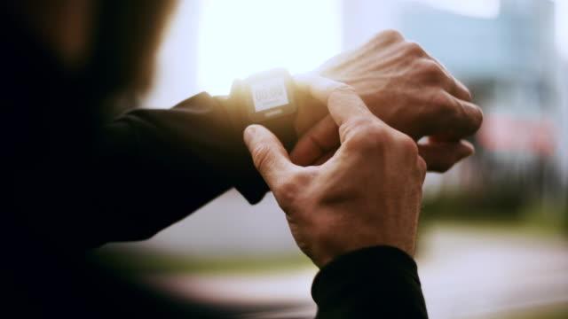 vidéos et rushes de 4 runner k départ smartwatch minuterie et la course. homme définissant une minuterie de traqueur de smartwatch avant de faire du jogging. gros plan pov - chrono sport