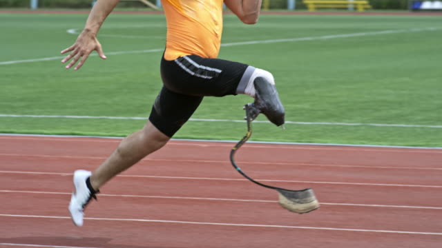 Runner With Prosthesis Training on Stadium Slow mo side view of amputee athlete with prosthetic blade running on stadium track outdoors prosthetic equipment stock videos & royalty-free footage