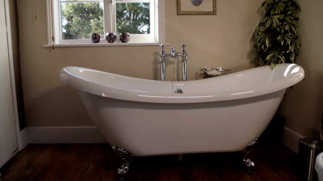 Running A Warm Soothing Bath Water flowing into a freestanding bath in slow motion. running water stock videos & royalty-free footage