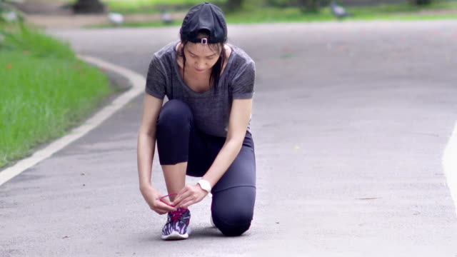 Running asian woman tying laces of running shoes before training video