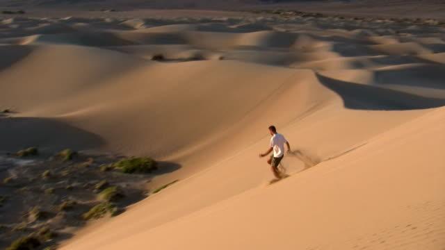 vídeos de stock e filmes b-roll de hd: running para baixo uma duna de areia - parque nacional do vale da morte