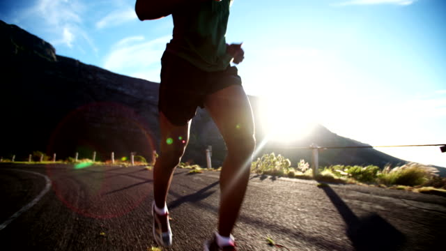 Running feet of male runner on mountain road in slow motion