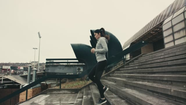 vídeos de stock e filmes b-roll de running in a wet weather - young woman running city
