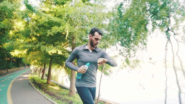 Running is part of my routine. Young athlete male dedicated to his daily running training. Slow motion scene. checking the time stock videos & royalty-free footage