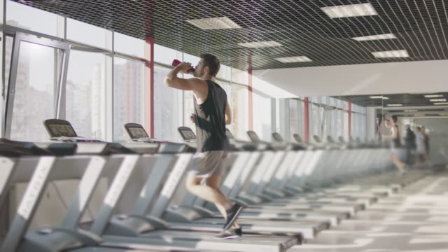 running man drinking water on treadmill machine in gym club. - runner rehab gym video stock e b–roll