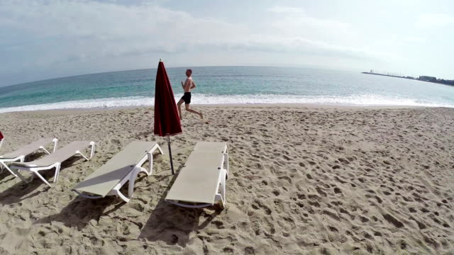 Running man on seaside with background of the sea. Flight and takeoff along, aerial view. France, Corsica. video