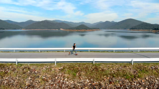 AERIAL Running man on the road with lake and mountain background video