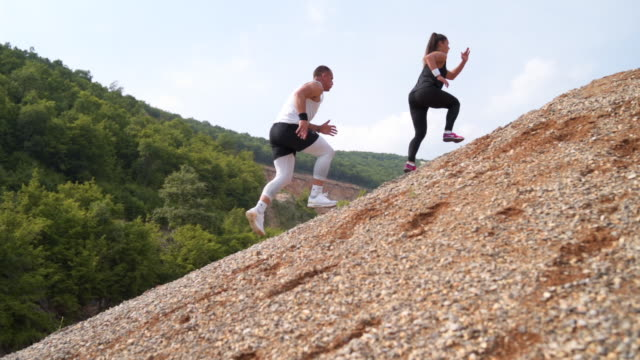 running on a rocky hill - irriducibilità video stock e b–roll
