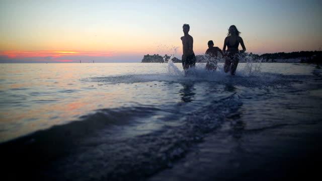 Running on beach on sunset video