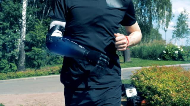 vídeos de stock e filmes b-roll de running person with artificial arm. human with a robot arm. - membro