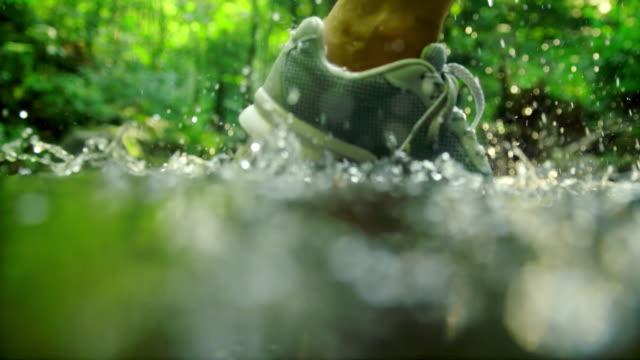 vidéos et rushes de slo mo running chaussure éclaboussure dans la rivière - joggeuse