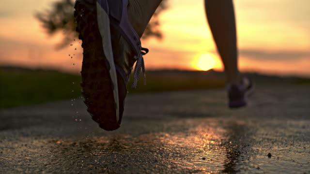濡れたアスファルトの上をはね slo mo を実行している靴 - 人の脚点の映像素材/bロール