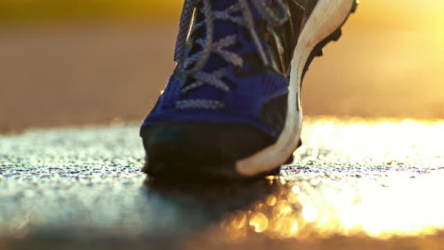 stockvideo's en b-roll-footage met slo-mo running schoen spatten op natte weg - running shoes