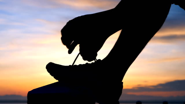 Running shoes - Man is tying shoe laces. male sport fitness runner getting ready for jogging outdoors the time during sunrise on dam road exercise. slow motion