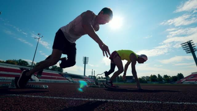 2人の障害のあるスポーツマンが行うランニングスタート - disabilitycollection点の映像素材/bロール