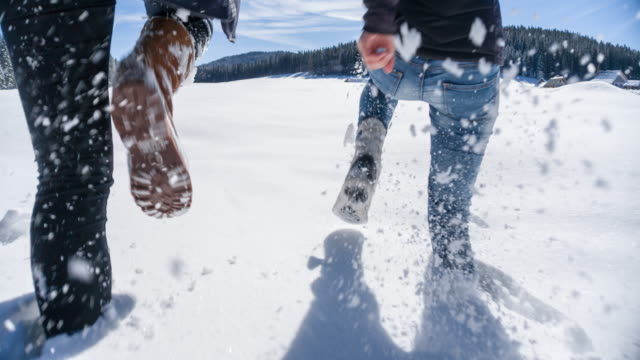 Running through snow Two young women running in fresh snow, enjoying their winter break, shot from the waist down recreational pursuit stock videos & royalty-free footage