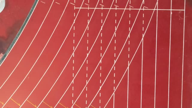 pista da corsa allo stadio, il colore è mattone arancione, vista ad angolo alto tramite drone. - atletico video stock e b–roll
