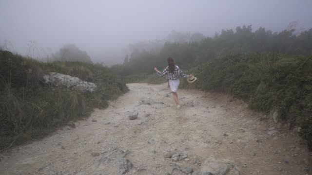 Running traveler girl in white dress, plaid t-shirt and staw hat runs in fog along country road. Windy. Sintra, Portugal.