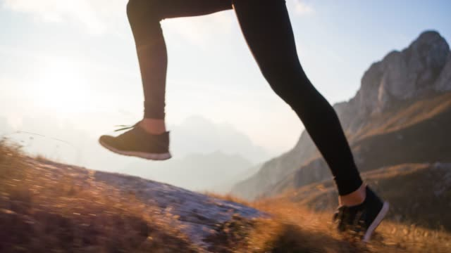 Running uphill in the mountains, illuminated by sunset light, view of athletes legs Fit athlete maintaining a healthy lifestyle, running uphill in mountain terrain over rocky trails and grassy slopes, illuminated by sunset light, shot from waist down, view of athletes legs human foot stock videos & royalty-free footage