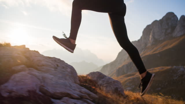 Running uphill over rocky trails and grassy slopes in mountain terrain
