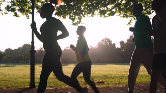 Running Group of friends running outdoors in the park in London. They are focused and determined. group of people stock videos & royalty-free footage
