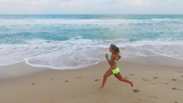 kör kvinna. kvinnliga löpare jogging utomhus tränar på stranden. vackra passar blandad ras fitness modell utomhus - tävlingsdistans bildbanksvideor och videomaterial från bakom kulisserna