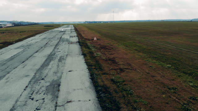 Runway in the fields and a small plane flying off it Runway in the fields and a small plane flying off it. 4K propeller airplane stock videos & royalty-free footage