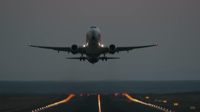 a runway with a taking off plane - decollare attività video stock e b–roll