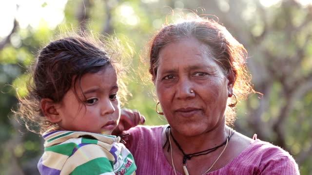 vídeos y material grabado en eventos de stock de asia rurales poco niño con la abuela en al aire libre. - aldea