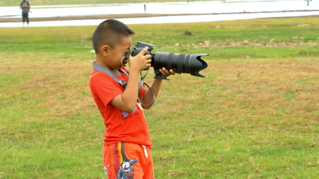 Rural boy holding a big camera