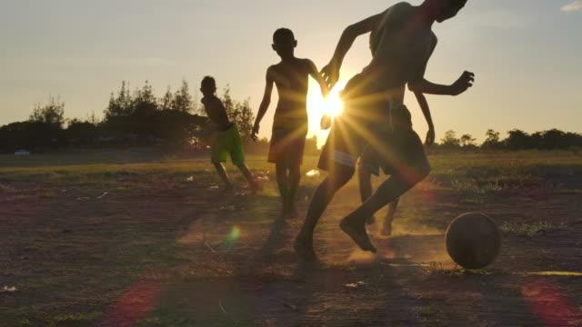 vídeos de stock, filmes e b-roll de as crianças rurais estão jogando o futebol no tempo do por do sol.slow o movimento - futebol