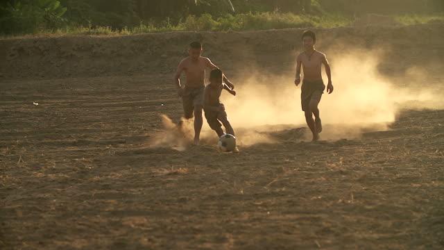 農村の子供たちは、村に五月晴れの日でサッカーを遊んでいます。 - 男の子点の映像素材/bロール