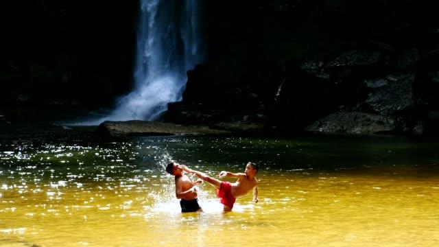 vídeos de stock e filmes b-roll de rural children practicing muay thai at waterfall. (slow motion) - boxe tailandês
