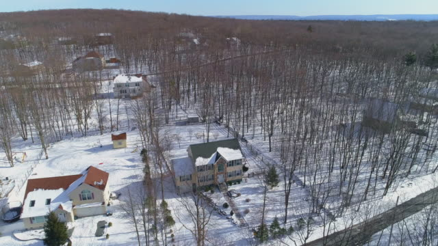 a rural community in pocono mountains, appalachian, in pennsylvania. aerial view on the cold sunny snowy winter day. - горы поконо стоковые видео и кадры b-roll