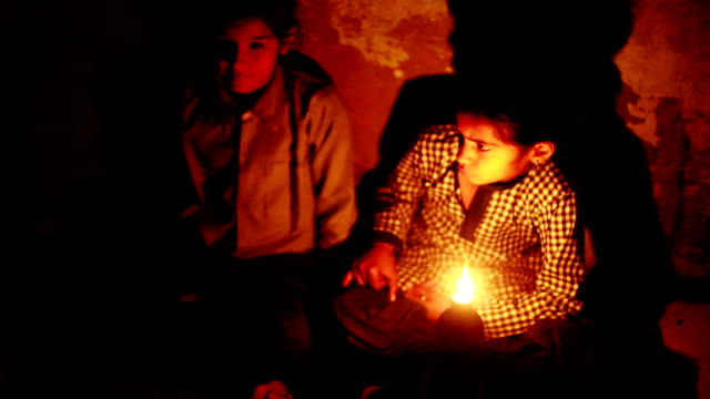 Rural girls studying in lantern at home Poor rural girls studying in lantern light at home, A small cup-shaped oil lamp made of baked clay is called diya in rural India. haryana stock videos & royalty-free footage