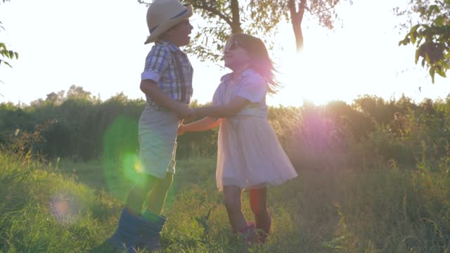 rural holidays, little boy and small girl circling and jumping holding hands at sunset - brother stock videos and b-roll footage