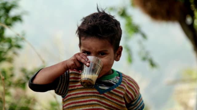 сельские индийские мальчик едят пищу с хлебом и чаем. - голодный стоковые видео и кадры b-roll