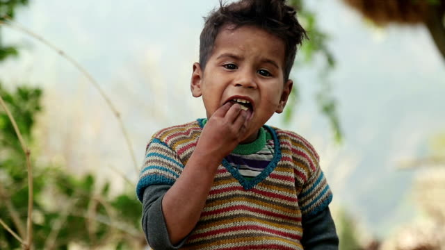 Rural Indian Boy Eating food having bread and tea. video shot of sitting poor dirty kid eating bread with tea in village. hungry child stock videos & royalty-free footage