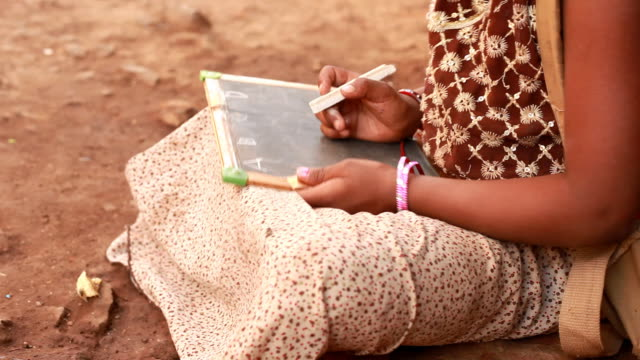 Rural Indian girl writing ABC on a Chalkboard video