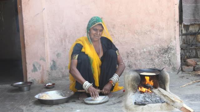 rural indian woman rolling dough - sari filmów i materiałów b-roll